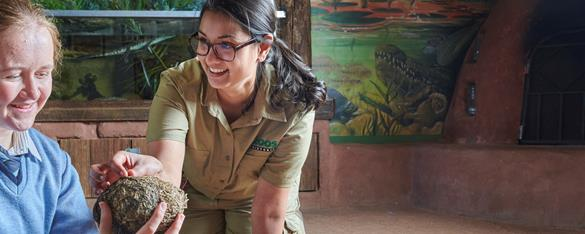 Female zoo education officer talking and smiling with a female student.