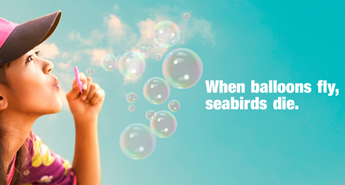 When Balloons Fly, Sea Birds Die campaign sign. Girl with pink hat blowing bubbles.