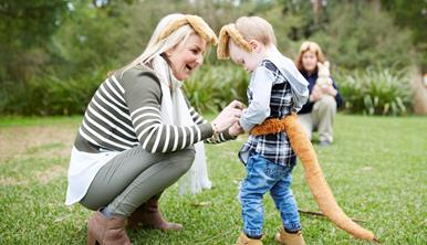 Mother and child standing on the lawn, dressing up as a Wallaby with ears and a tail.