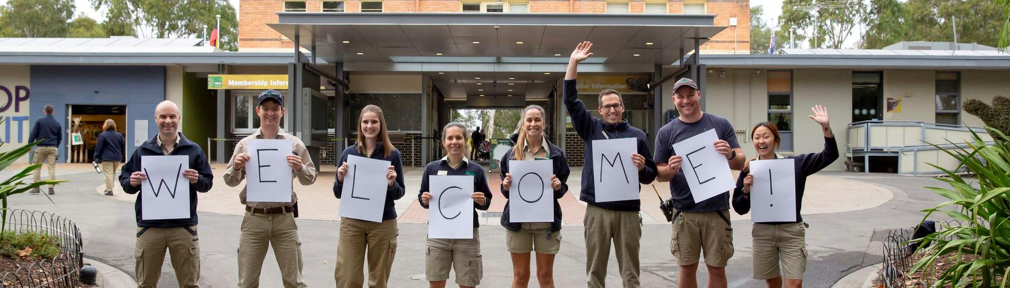 Eight zoo staff members standing in a line holding up letters spelling welcome!