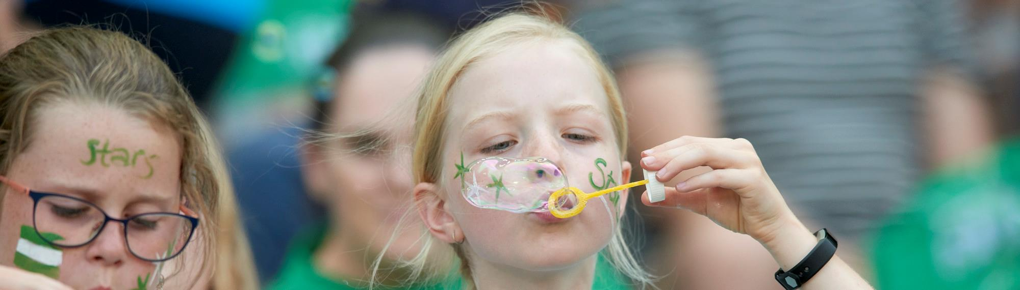 Young girl wearing face paint blowing bubbles for the Bubble World Record Attempt.