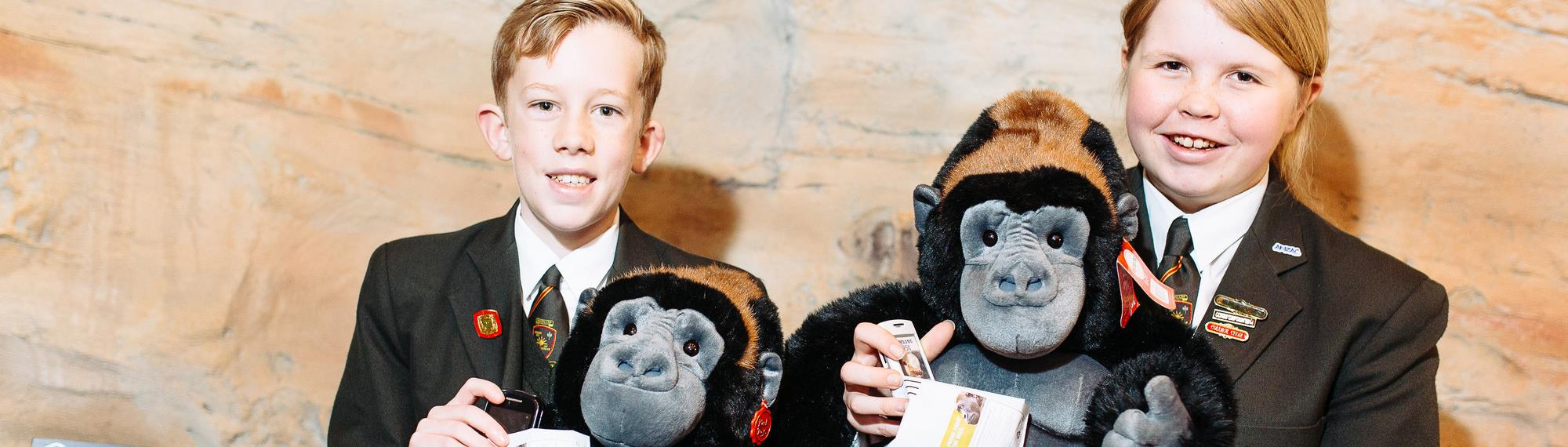 Two students holding plush gorillas standing next to a phone recycle bin.