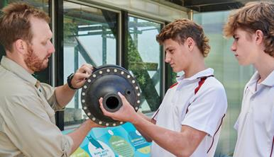 Two high school students with Melbourne Zoo educator investigating an object.