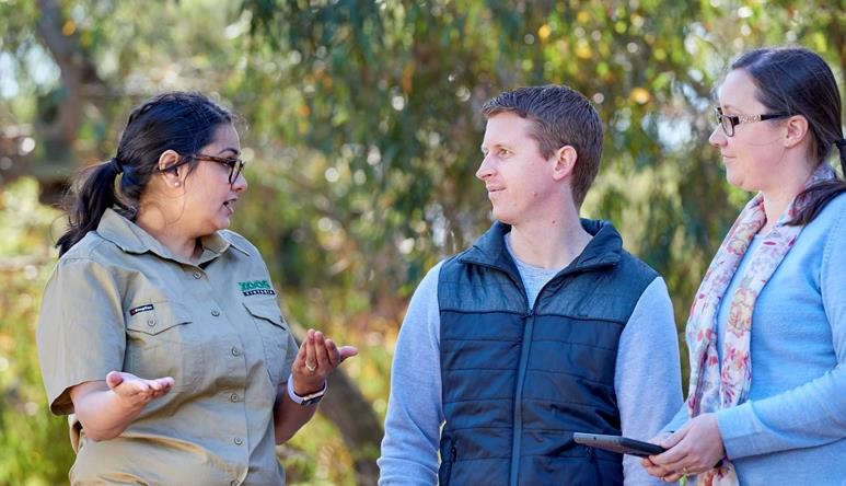 Two adults listening to a keeper chatting at Werribee Open Range Zoo.
