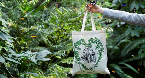 Totes for Wildlife bag being held up with a green foliage back ground.