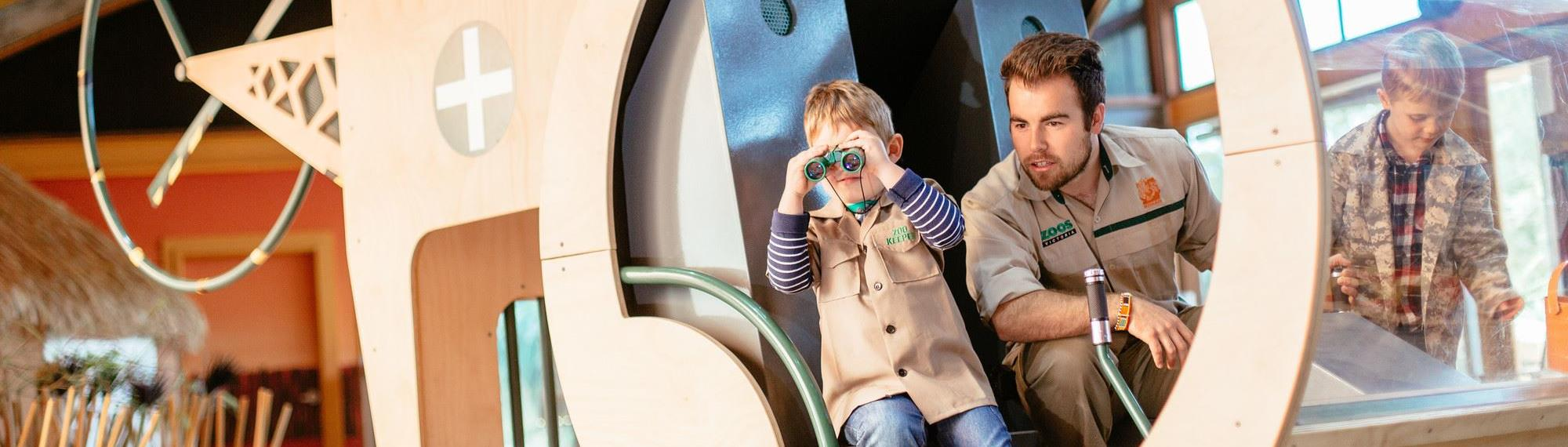 Child looking through binoculars with safari guide playing in a wooden helicopter in Ranger Kids indoor play centre.