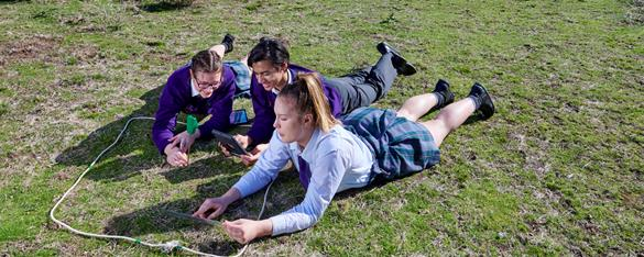 Three secondary students laying on the grass, using a moisture prob to study the grasslands of Werribee Open Range Zoo.
