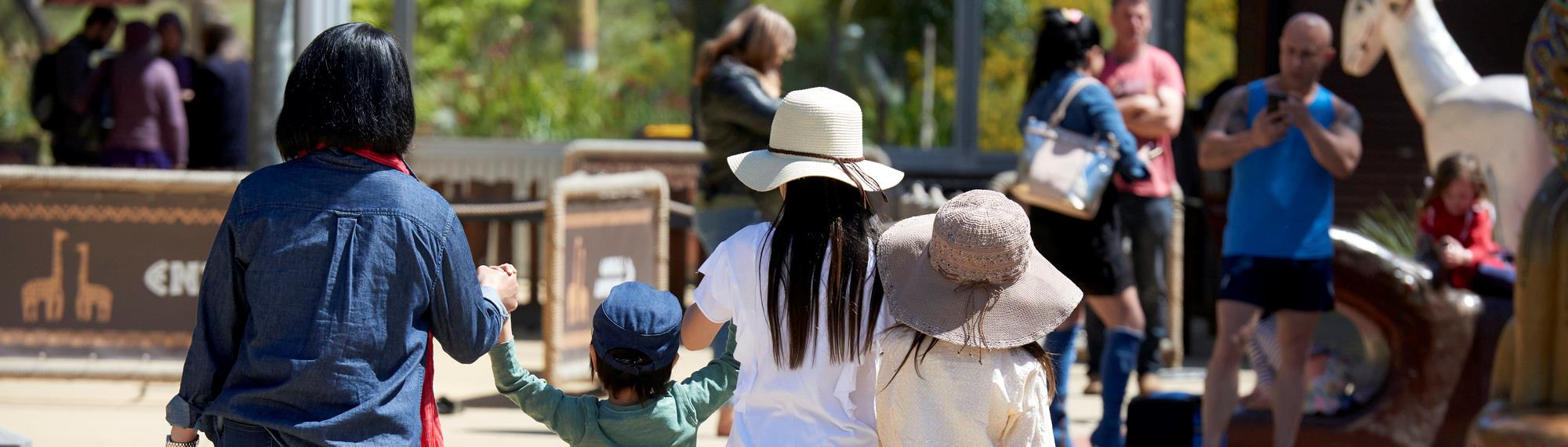 Family day out at Werribee Open Range Zoo. Visitors walking towards the entrance gate holding hands with young children.