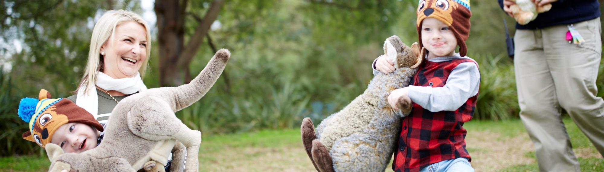 Mother laughing with her two kids who are playing with plush toy wallabies on Wallaby Wednesday at Healesville Sanctuary.