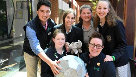A small group of students and zoo staff smiling for the camera while holding a grey ball and a plush toy elephant.