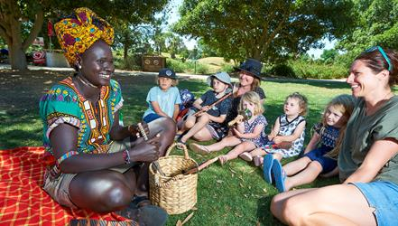 Smiling staff member, Agum, dressed in traditional African attire sitting on a rug engaging visitors with handmade African musical instruments. Two women and five children are enjoying watching her demonstration.