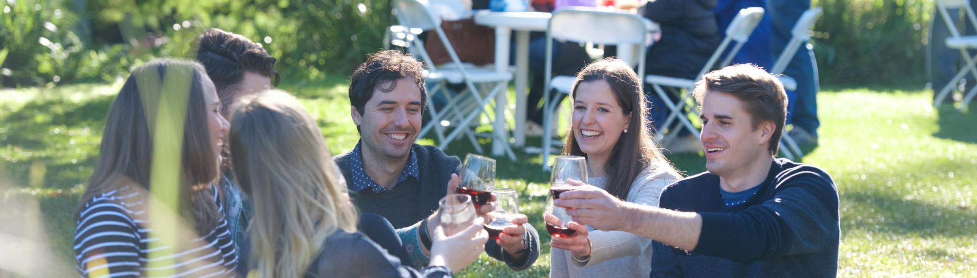Group of six young adults sitting on a picnic rug, in the gardens of Healesville Sanctuary, making a toast with red wine at Wine and Wildlife.