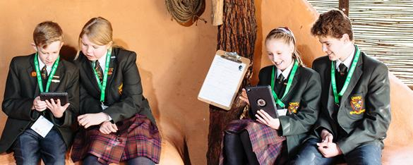 Four students looking at their Ipads while studying in a ranger hut.