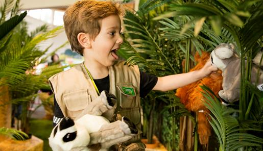 Young boy dressed as an explorer playing with plush toys amongst palm trees.