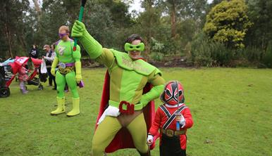 Crapman and dressed up child posing for the photo on the lawn. Zooperman and other visitors in the background.