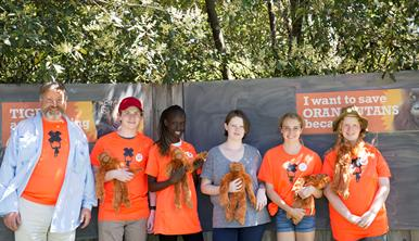 A smiling man and five students holding plush orang-utans in front of a sign that say I want to save orang-utans. Five are wearing orange Don't Palm Us Off campaign T shirts..