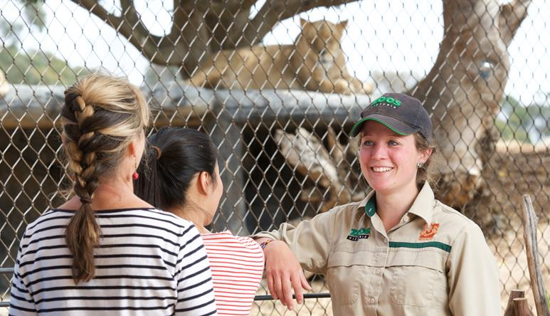 Smiling Lion Keeper chatting to two young women at the Lion Presentation. Lion enclosure in the background.