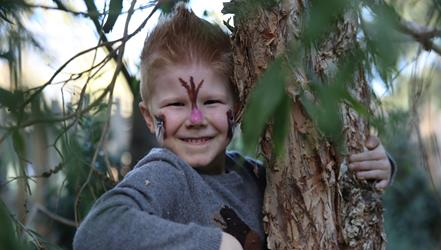Smiling boy pretending to be a possum climbing a tree with possum face paint.